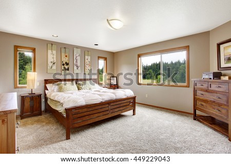 Cozy bathroom interior with double wooden bed and beige carpet floor. - stock photo
