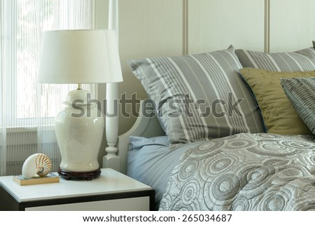 cozy bedroom interior with pillows and reading lamp on bedside table - stock photo