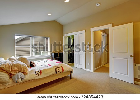 Cozy bedroom with high vaulted ceiling and walk in closet. Light wooden bed with white cheerful bedding - stock photo