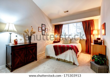 Cozy bedroom with high vaulted ceiling furnished with antique cabinet and queen size bed - stock photo