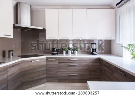 Cozy beige kitchen interior with wooden cupboards - stock photo