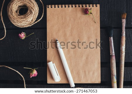 Cozy blank sheet mockup. Blank paper with artist brushes on wooden table with cup and camera. Selective focus photo with Shallow DOF. Flat lay top view. - stock photo