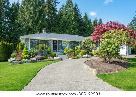 Cozy blue house with beautiful landscaping on a sunny day. Home exterior. - stock photo