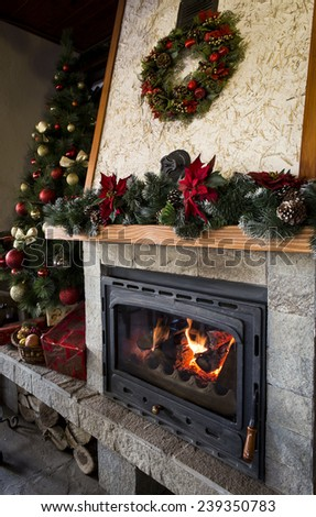 Cozy burning fireplace with christmas decorations - stock photo