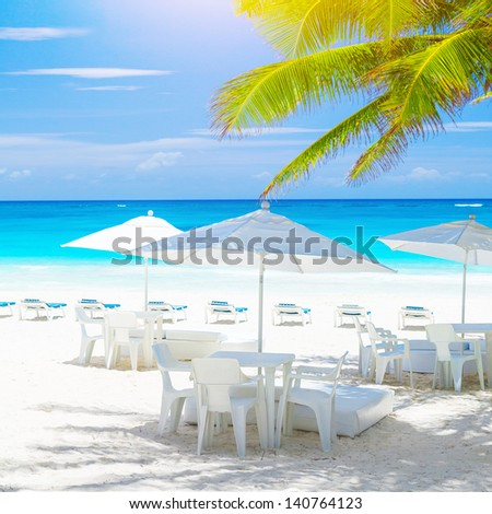 Cozy cafe on sandy sea shore, beautiful sea landscape, clean white chairs and tables under umbrellas, fresh green palm tree, luxury tropical resort, summer vacation concept  - stock photo