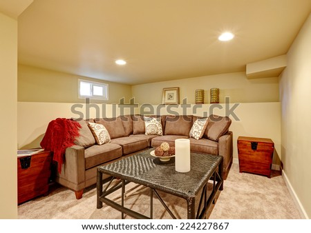 Cozy family room with brown comfortable sofa and wicker table. Room with light ivory walls and carpet floor - stock photo