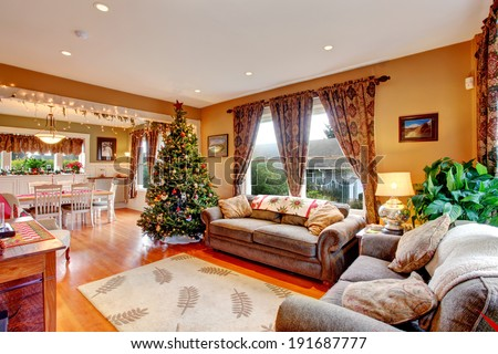 Cozy house interior on Christmas eve. View of living room with Christmas tree and dining area - stock photo