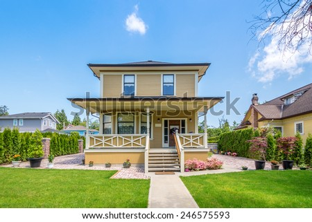 Cozy house with beautiful landscaping on a sunny day. Home exterior. - stock photo