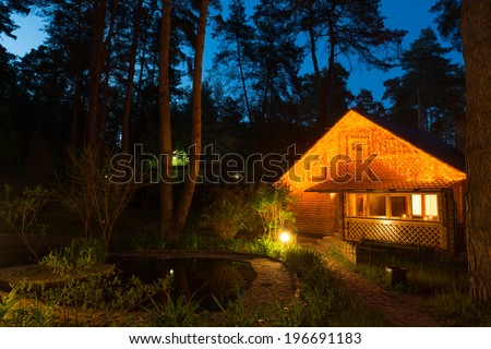 Cozy houseby the pond in the conifer forest at night - stock photo