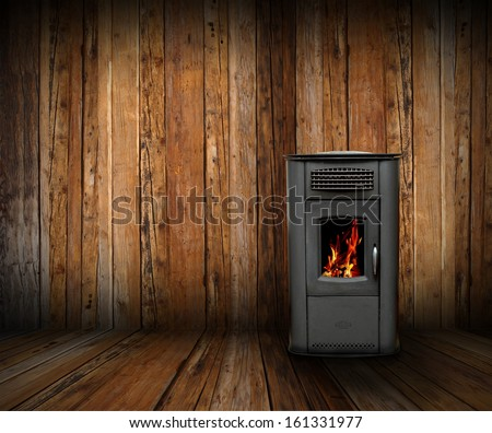 cozy interior backdrop of a wooden lodge with burning stove - stock photo