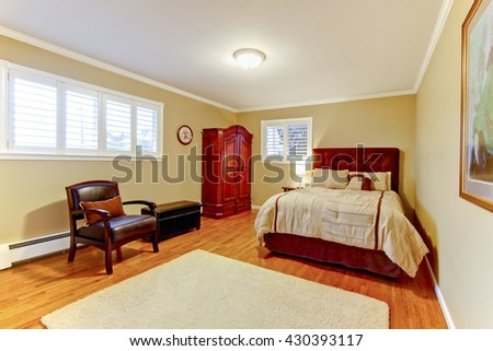Cozy large guest room with suede brown bed and armor, hardwood floors. - stock photo