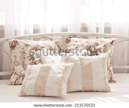 Cozy light pillow on bed - stock photo