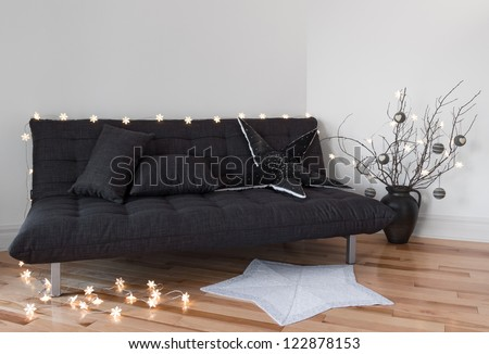 Cozy lights in the living room decorating sofa and tree branches. - stock photo