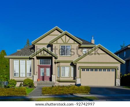 Cozy luxury suburbs home exterior against blue sky - stock photo