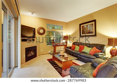 Cozy medium sized living room with carpet, lather recliner and sofa. - stock photo