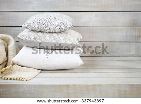 Cozy pillows and plaid on the light wooden background. Close up - stock photo