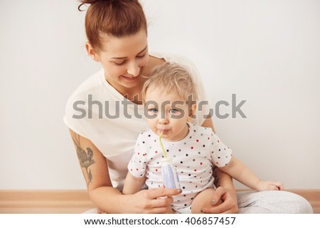 Cozy scene of happy Caucasian family spending time together, playing, hugging, smiling. Attractive young mother with her lovely kid on her laps, sitting on the floor at home against white background  - stock photo