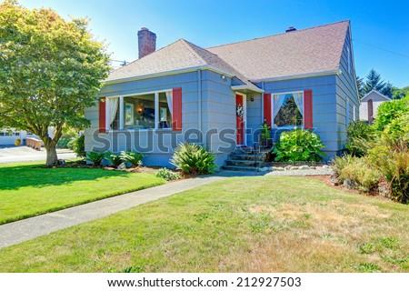 Cozy small house exterior with red details. View of entrance porch and walkway - stock photo