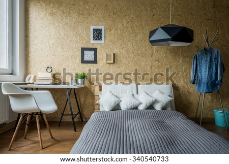 Cozy teenage bedroom with trendy wooden wall - stock photo