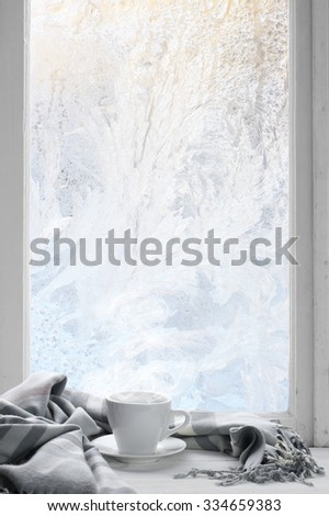 Cozy winter still life: cup of hot coffee with warm plaid on windowsill against frost pattern on window. - stock photo