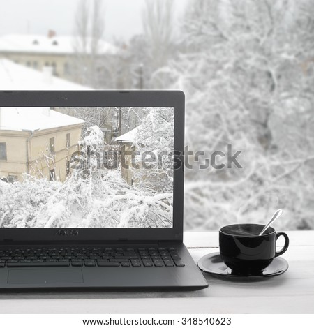 Cozy winter still life: laptop with outside view on screen and cup of hot coffee against snow landscape in window. - stock photo