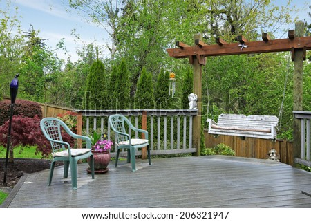 Cozy wooden deck with two old chairs and garden swing - stock photo