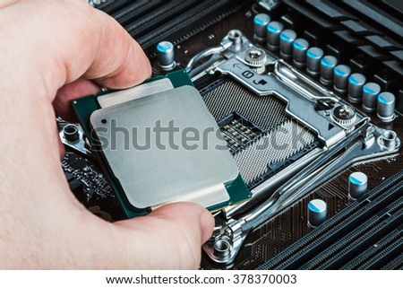 CPU in hand before installation into the motherboard - stock photo