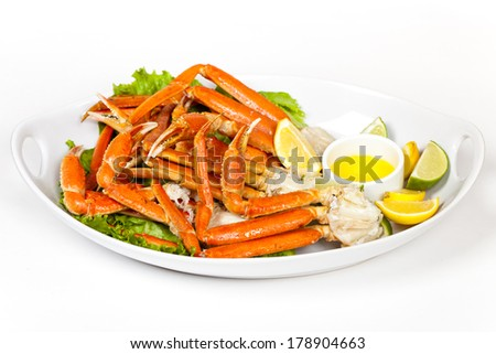 Crab Legs with fresh lemon slices and butter sauce - stock photo