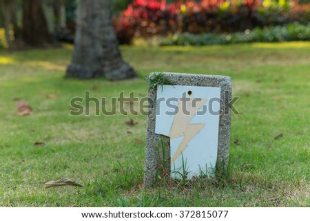Crack high voltage warning sign on stone post. - stock photo