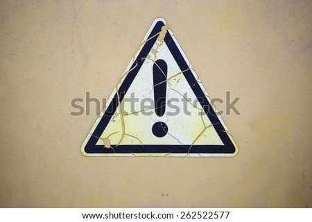 cracked adhesive label with a warning triangle on grungy ocher metal plate. concept for danger - stock photo