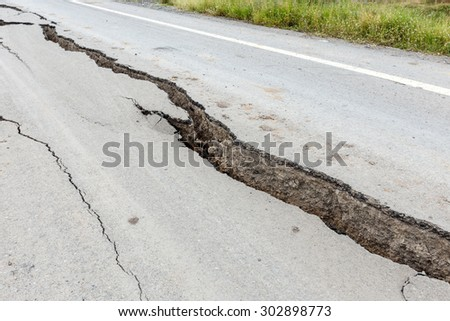 Cracked and broken asphalt road from earthquake. - stock photo