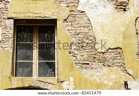 Cracked and dilapidated wall of an old house - stock photo