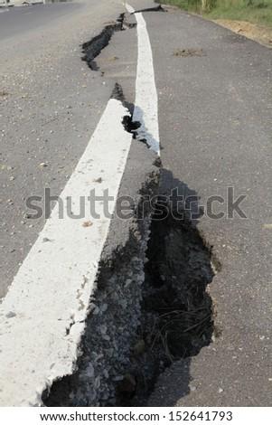 cracked asphalt road after flood  - stock photo