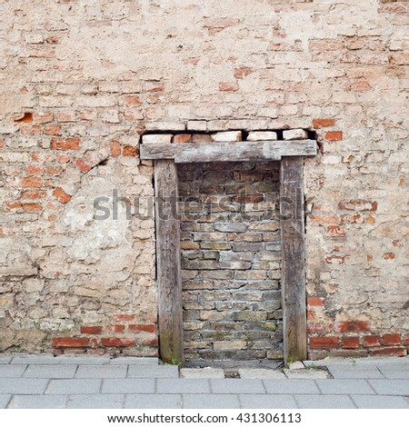 cracked brick wall with bricked up doorway of an abandoned house - stock photo