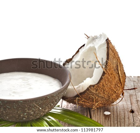 cracked coconut with milk cream in a clay bowl on wooden table - stock photo