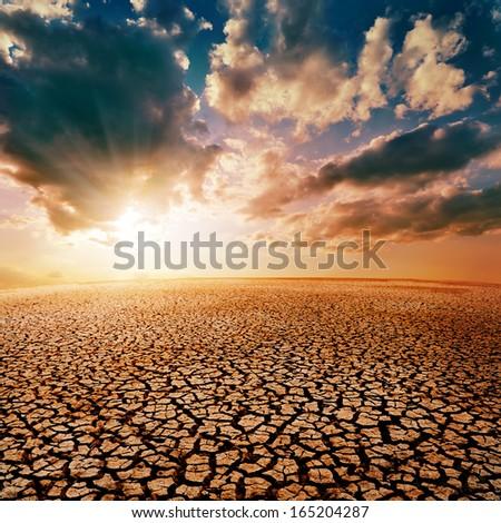 cracked desert and dramatic sunset - stock photo