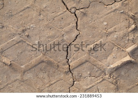 Cracked earth texture. Track car tires - stock photo