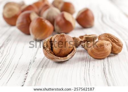 Cracked hazelnuts on white wooden background - stock photo