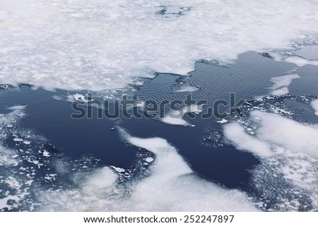 Cracked ice floes on a frozen sea, winter cold background - stock photo