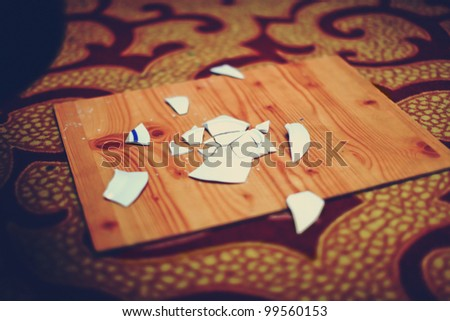 Cracked plate with many pieces on a wooden board. This is a wedding tradition. - stock photo