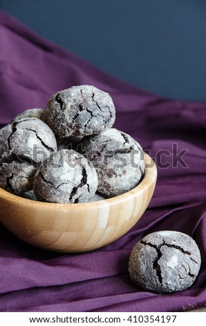 Cracked shortbread cookies in wooden bowl, on purple napkin. Selective focus. - stock photo