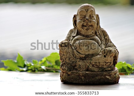 Cracked surface of old Buddha statue, decline of Buddhism concept. Fat Buddha home decor ornament. - stock photo
