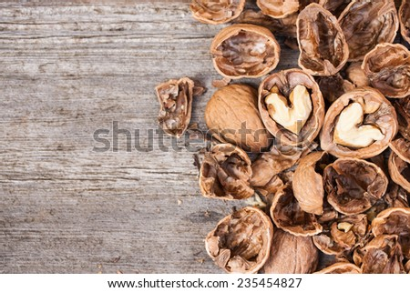 Cracked walnuts on wooden background, close up. Heart shape. Copy space. Also available in square format.  - stock photo