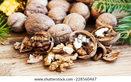 Cracked Walnuts, Walnuts Kernels with Whole Walnuts in the Background - stock photo