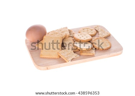 crackers and egg on chopping board isolated white background - stock photo