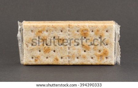 Crackers in plastic, isolated on a grey background - stock photo