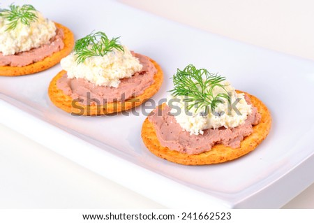 Crackers with pate, cheese cream and dill on a plate - stock photo