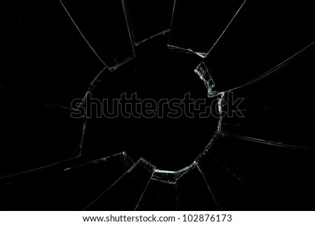 Crackled and broken window against a black background - stock photo