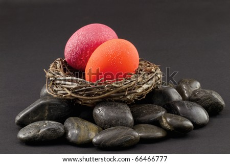 Crackled red and fluorescent orange nest eggs in a twig nest on rocks,   alarm and danger in investment environment and portfolio; it's time for fresh evaluation; how are your nest eggs doing? - stock photo