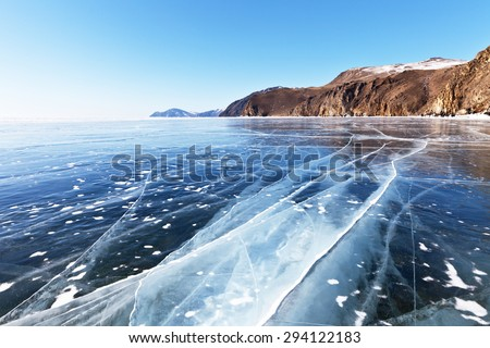 Cracks in the smooth surface of the ice of Lake Baikal - stock photo
